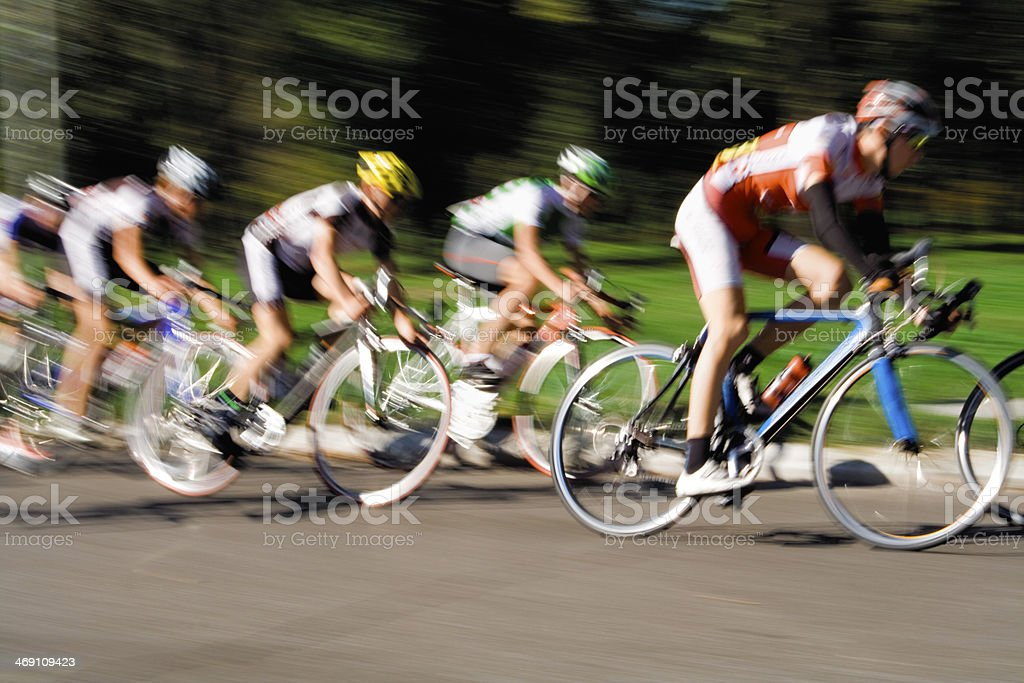 A blurred motion shot of racing cyclists on a street stock photo