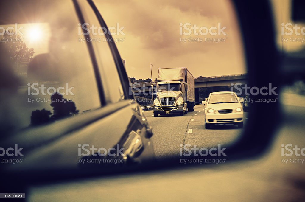 Blurred motion view in the car lateral mirror at sunset royalty-free stock photo