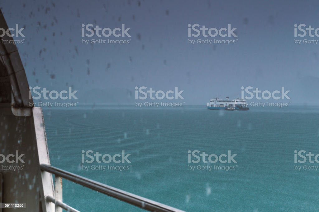 Blurred of the boat float in the sea, In the rainy day. stock photo