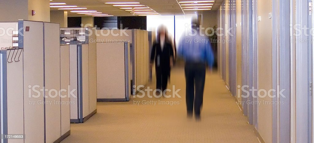 Blurred office workers walking down a corridor with cabinets royalty-free stock photo