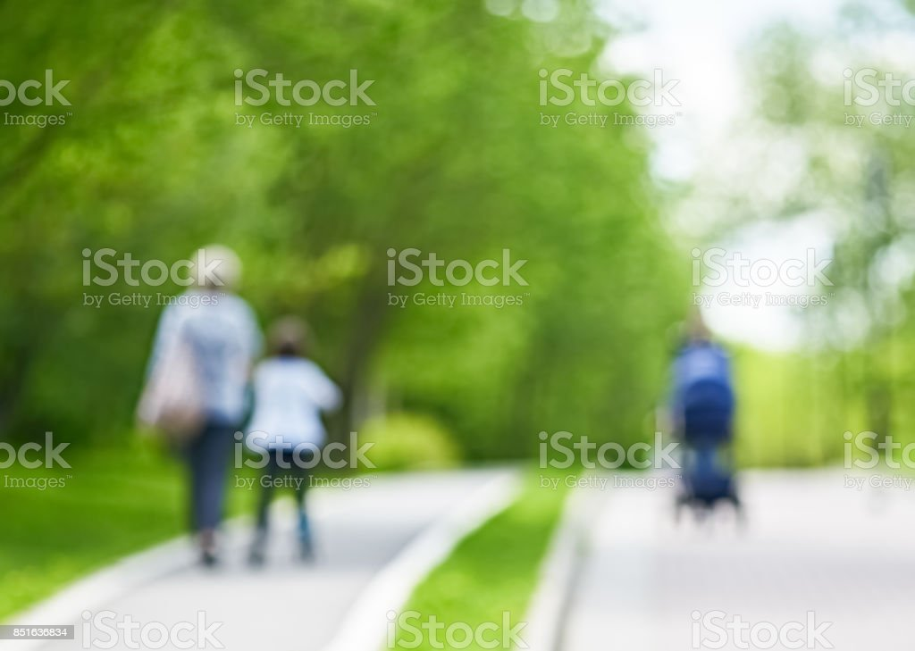 blurred park background with walking people stock photo