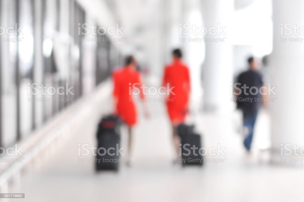 Blurred people and flight attendants walking at the airport hall stock photo