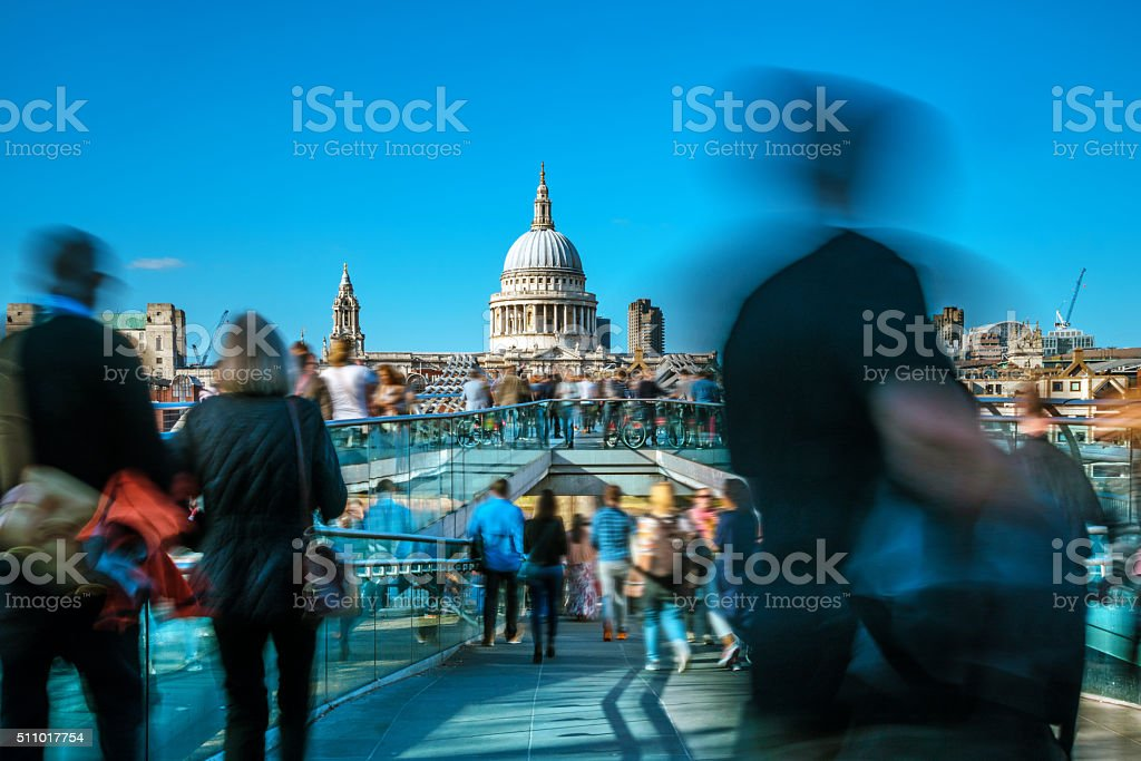 blurred People crossing Millenium Bridge in London stock photo