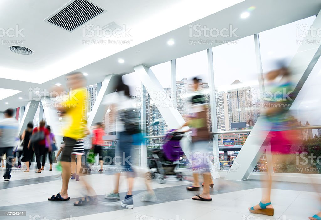 Blurred people in motion in a walkway stock photo