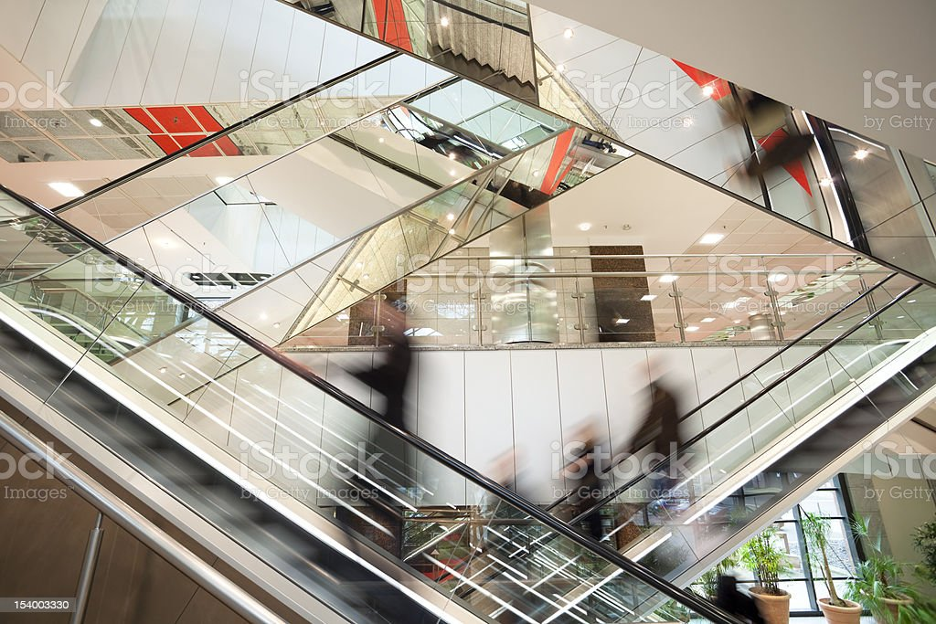 Blurred People on Escalator in Modern Glass Interior stock photo