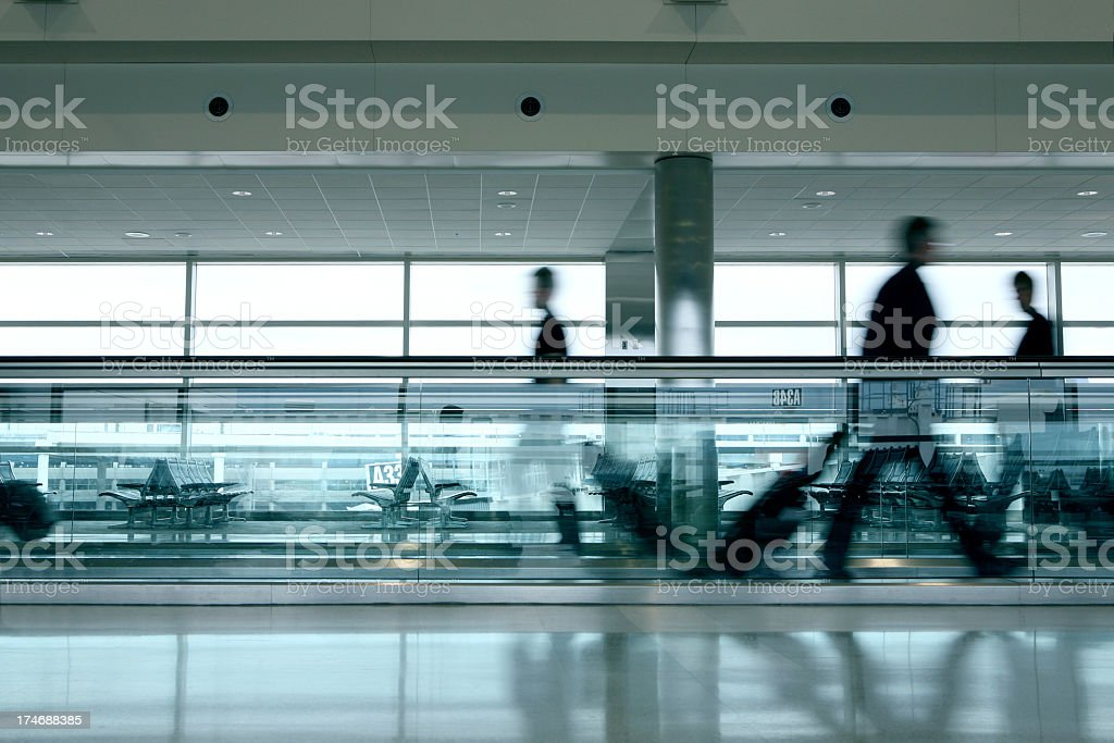 Blurred people waking on travelator at airport royalty-free stock photo