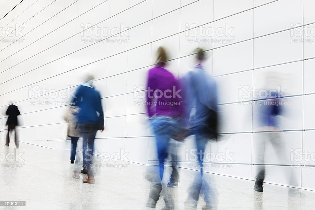 Blurred People Walking Down Futuristic Hallway royalty-free stock photo