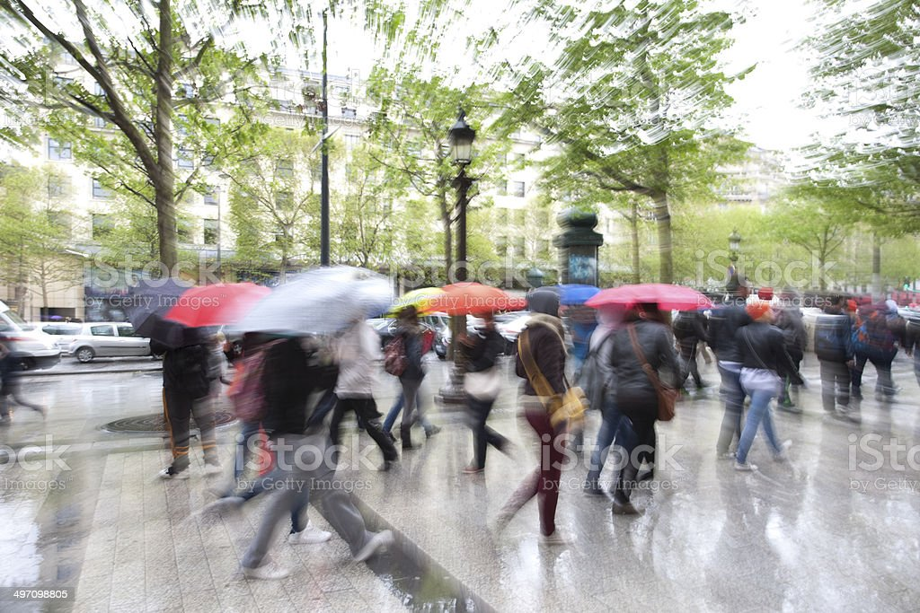 Blurred People Walking in Rain Down Street stock photo