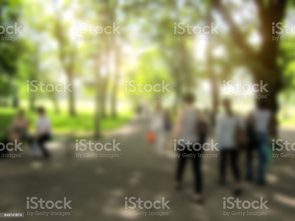 Blurred people walking in the park stock photo