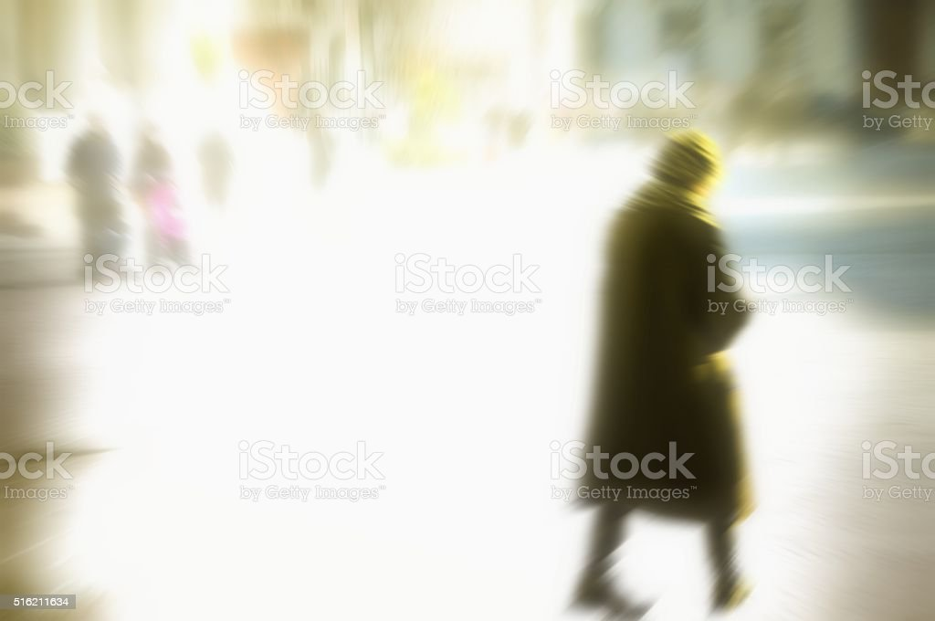 blurred people walking in the street. Elderly woman in closeup. stock photo