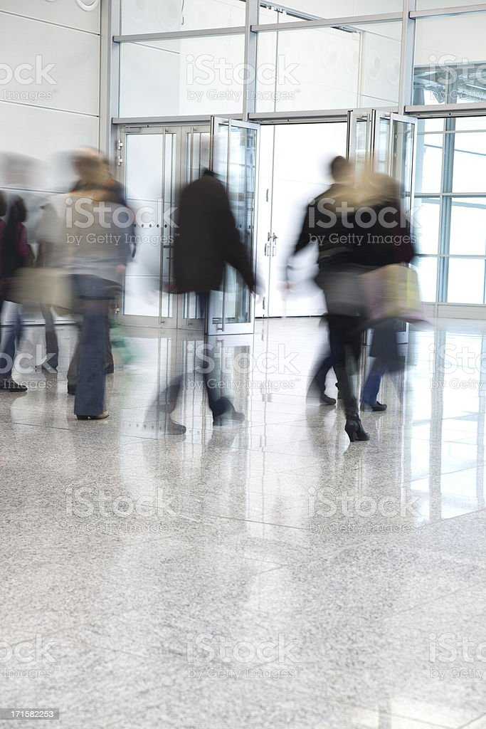 Blurred People Walking Through Glass Doors royalty-free stock photo