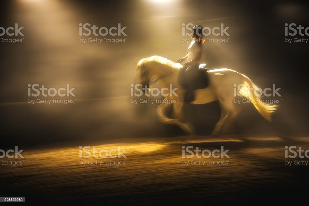 Blurred photo of a woman riding a horse at night stock photo