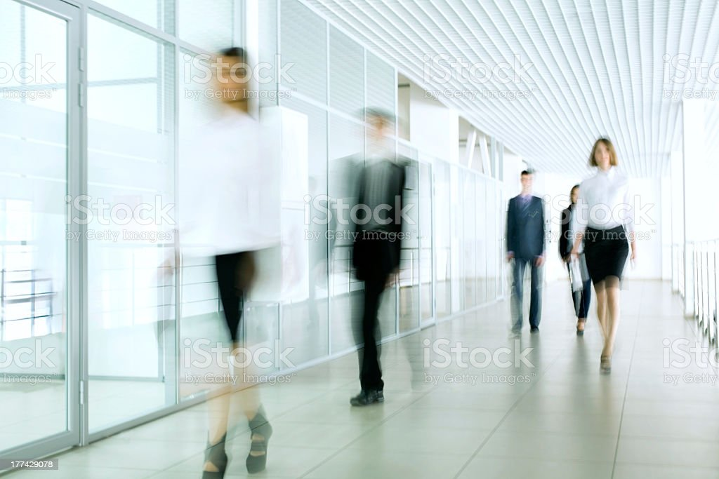 A blurred photo of business people in an office stock photo