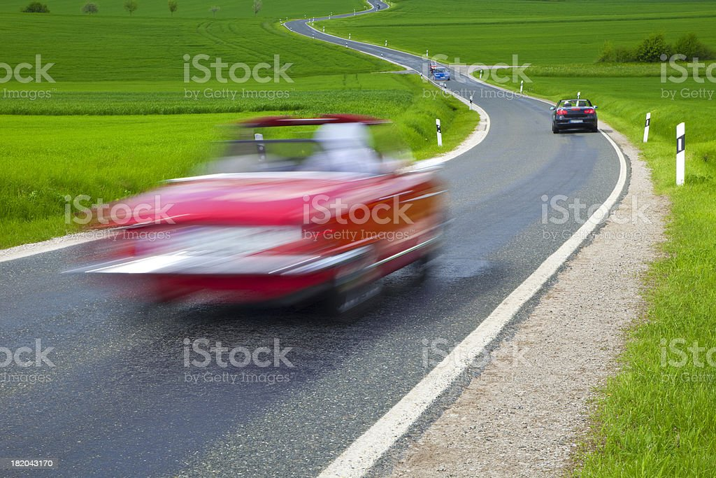 Blurred Red Car Driving on Winding Road in Spring Landscape royalty-free stock photo
