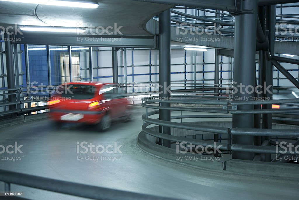 Blurred Red Car in Spiral Exit from Parking Garage royalty-free stock photo