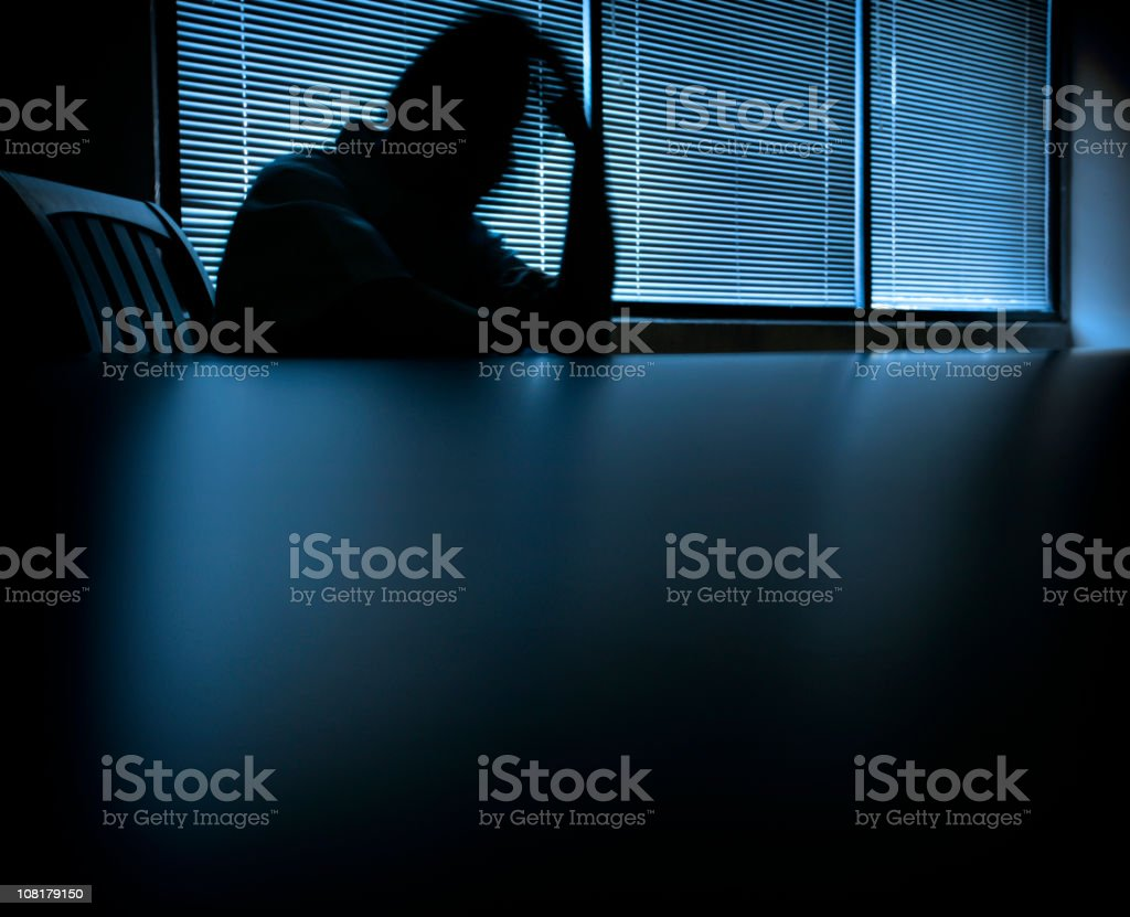 Blurred Shadow of Man Holding Head at Table stock photo