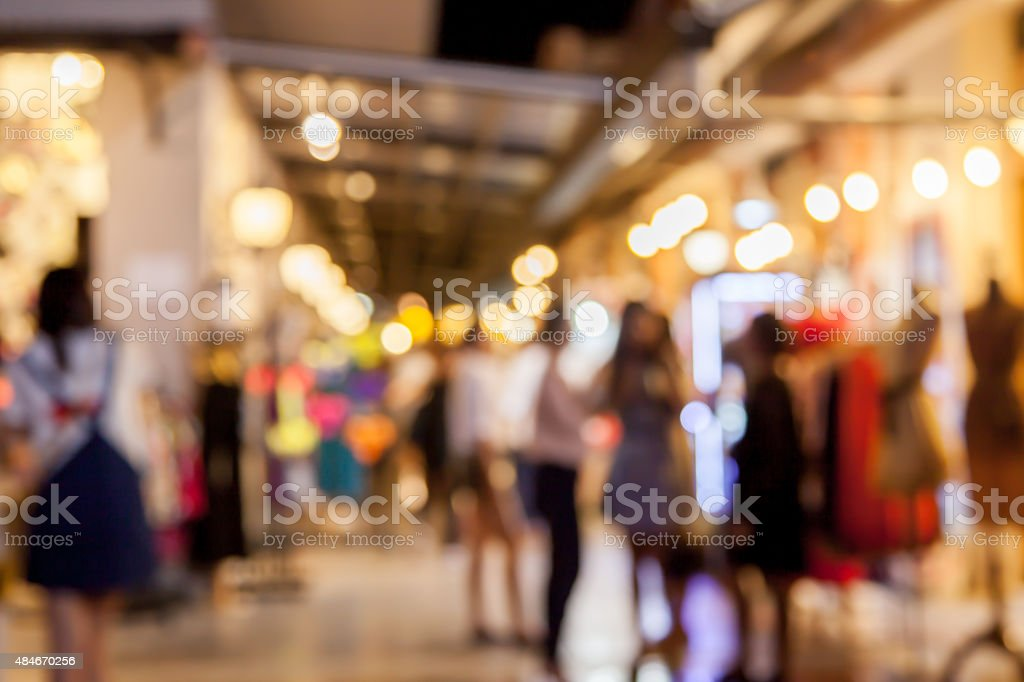 blurred shop and people in public night market with bokeh stock photo