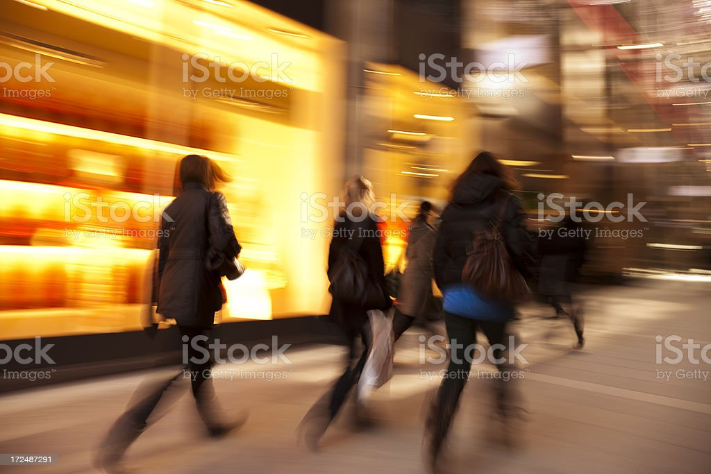 Blurred Shoppers Passing by Illuminated Shop Window at Dusk stock photo