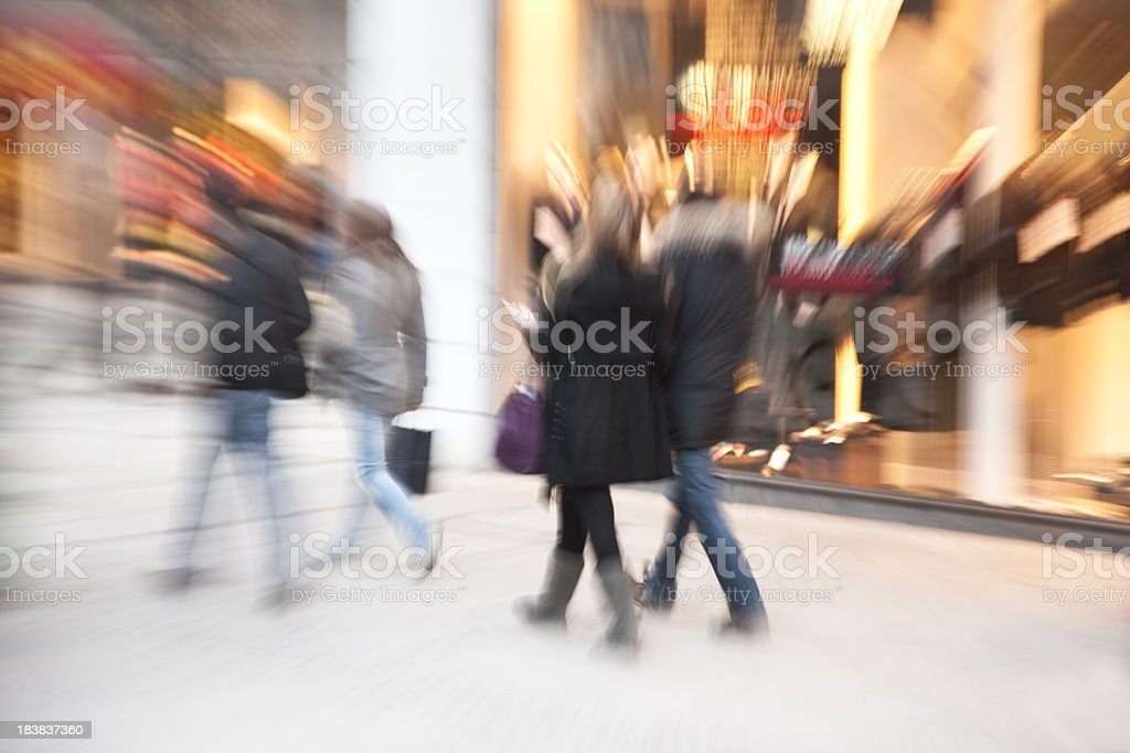 Blurred Shoppers Passing by Illuminated Shop Window at Dusk royalty-free stock photo