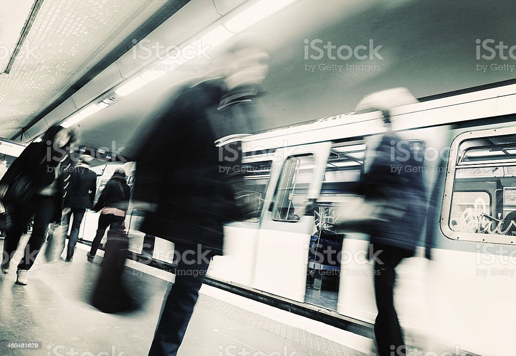 Blurred shot of passengers at a train station with train royalty-free stock photo