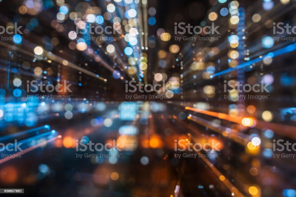 Blurred skyscrapers by night with bokeh lights trail stock photo