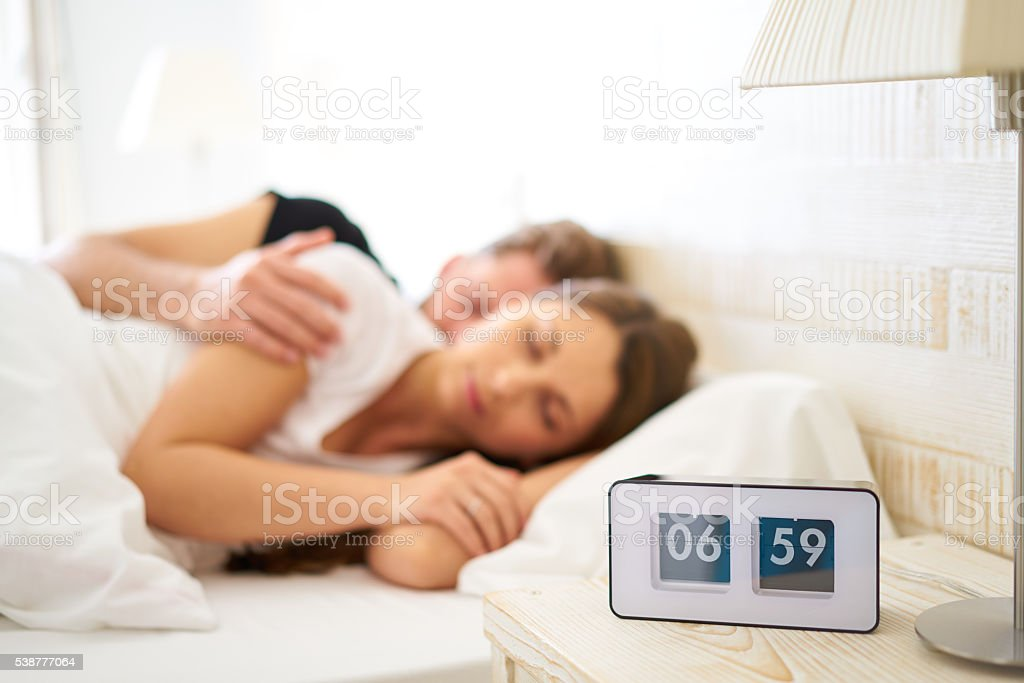 blurred sleeping couple with flip clock stock photo
