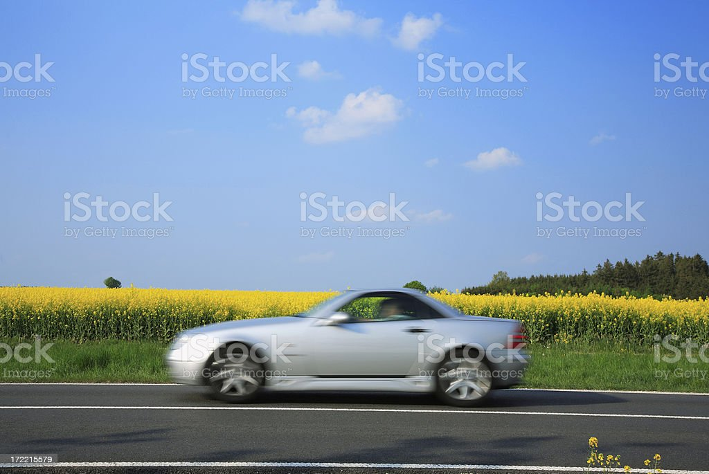 Blurred Sports Car Driving Through Summer Landscape royalty-free stock photo