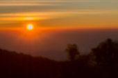 Blurred sunset behind the mountain with flare  background