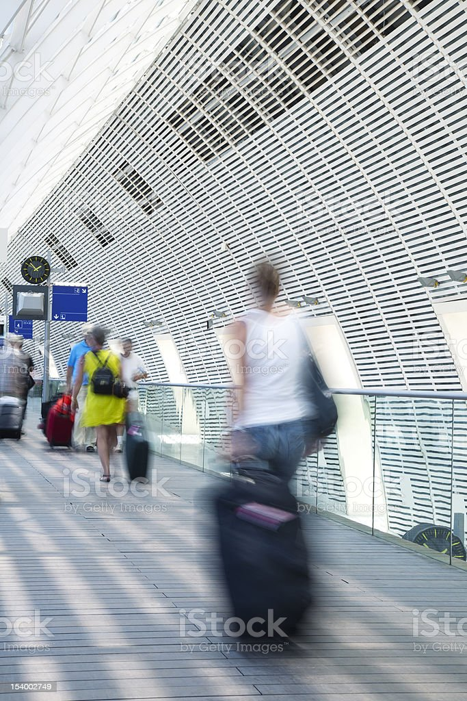 Blurred Travellers Pulling Suitcase Along Hallway in Train Station royalty-free stock photo