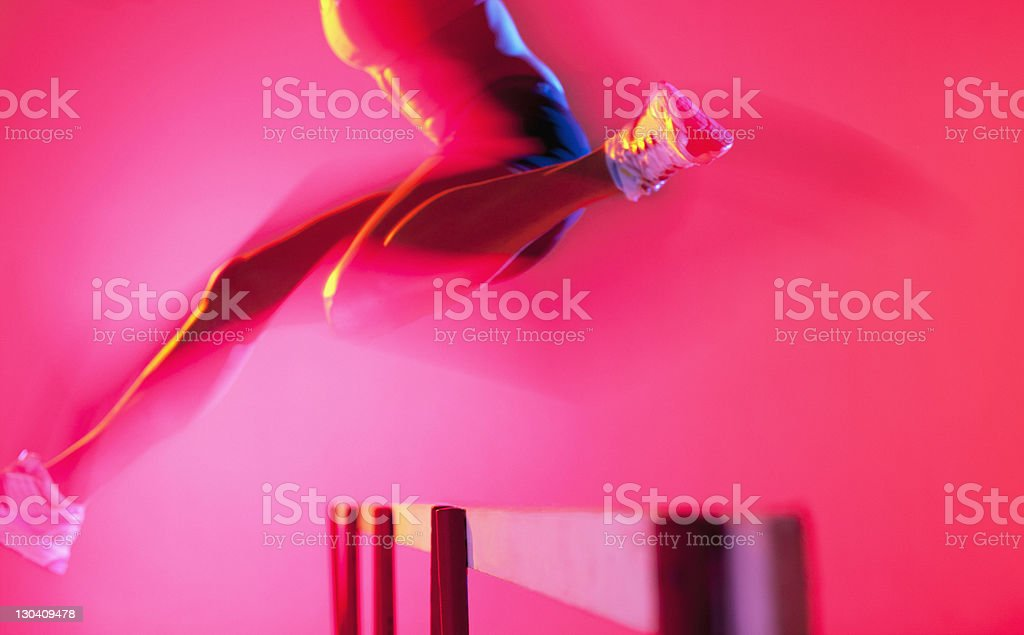 Blurred view of athlete jumping hurdle royalty-free stock photo