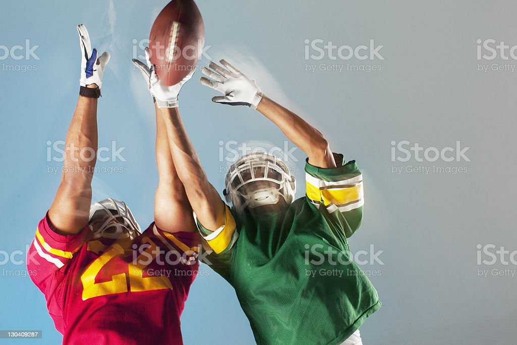 Blurred view of football players reaching for ball royalty-free stock photo
