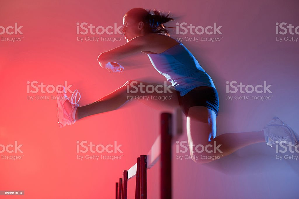 Blurred view of runner jumping hurdles stock photo