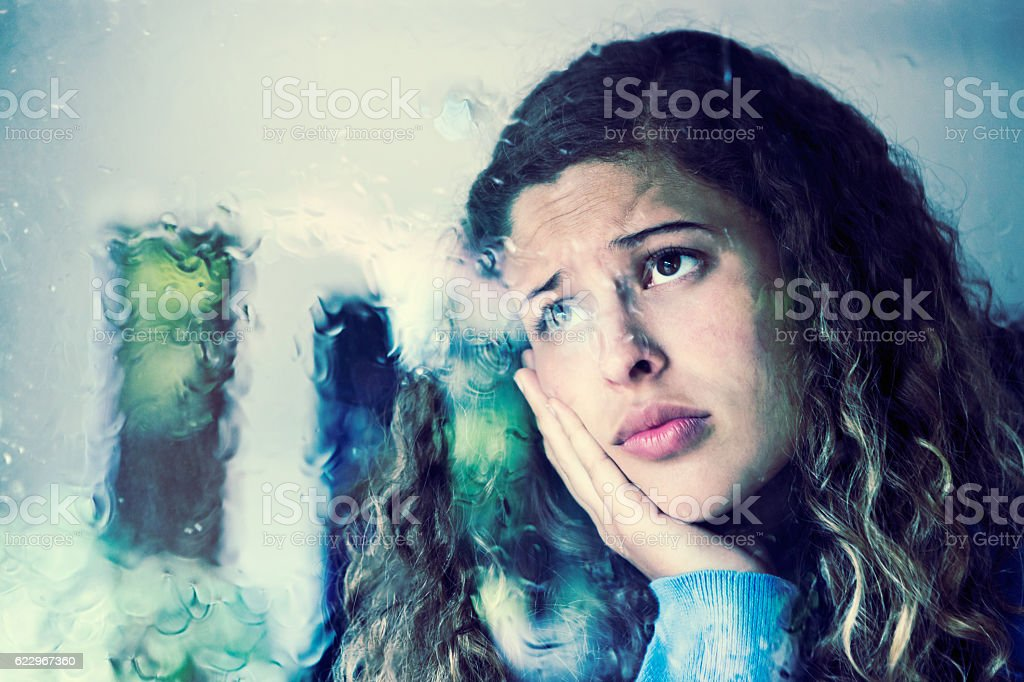 Blurred view of unhappy young beauty behind rain-streaked glass stock photo