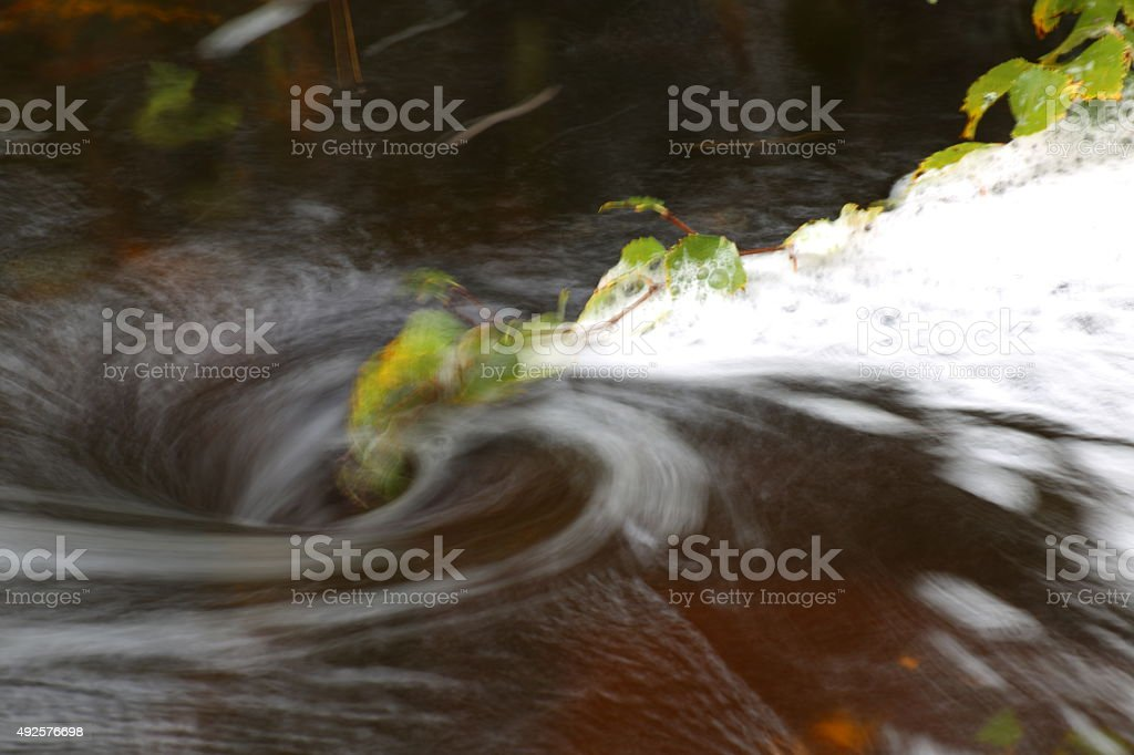 Blurred vortex in water with spray and a birch twig stock photo