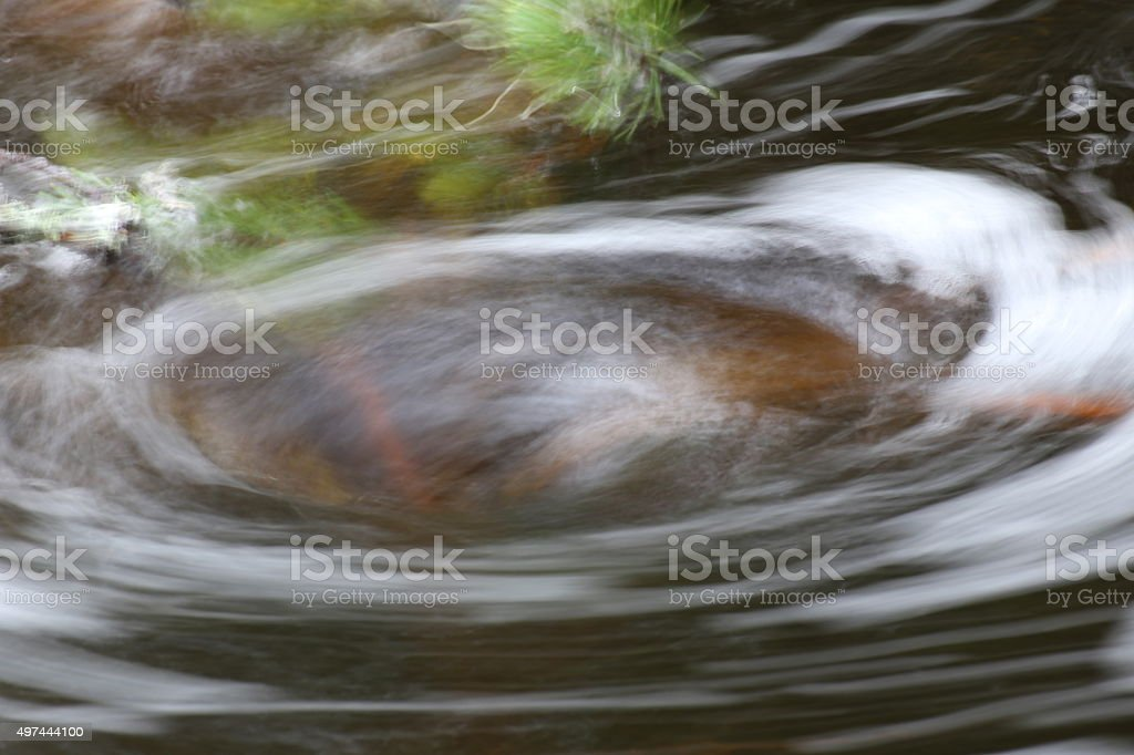Blurred vortex in water with spray and plant parts stock photo