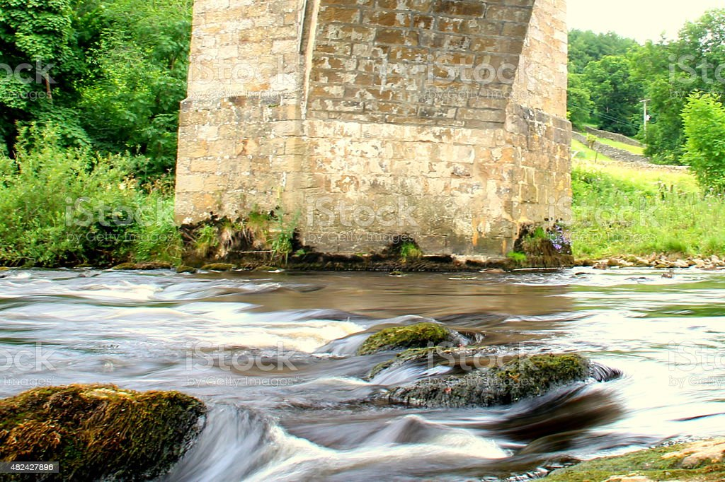 Blurred water, river wharfe, North Yorkshire, UK, under stone bridge stock photo