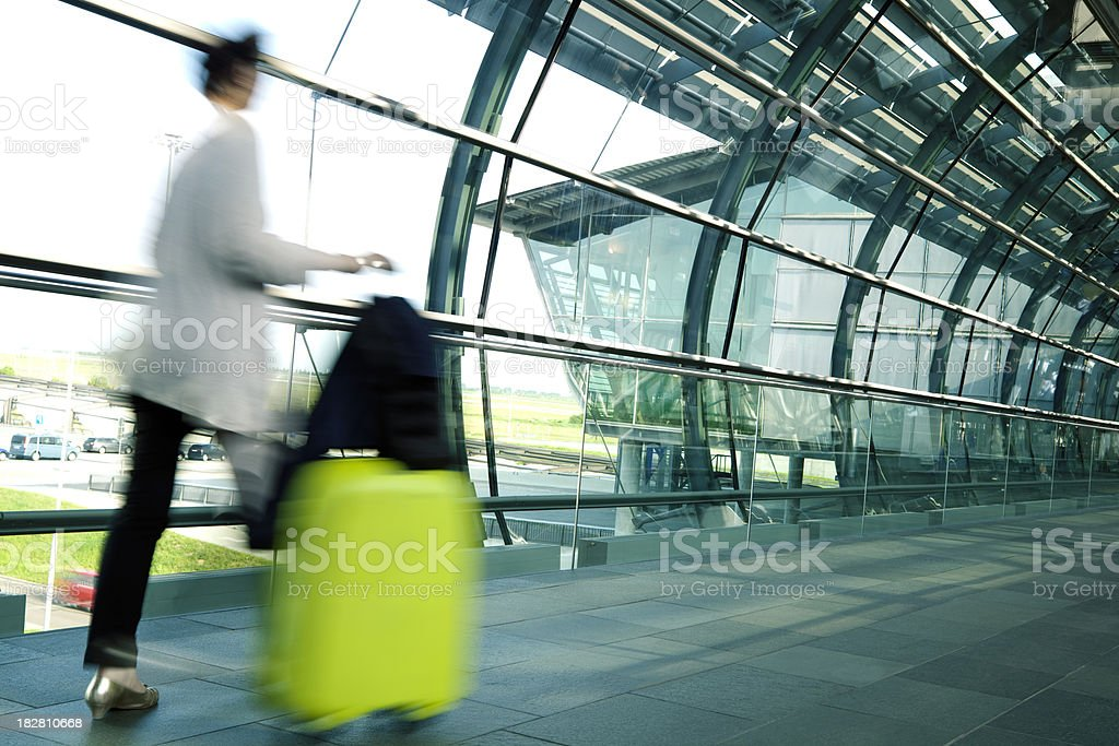 Blurred Woman Pulling Suitcase Allong Hallway in Airport royalty-free stock photo
