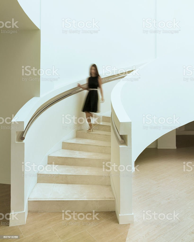 Blurred woman walking down staircase stock photo