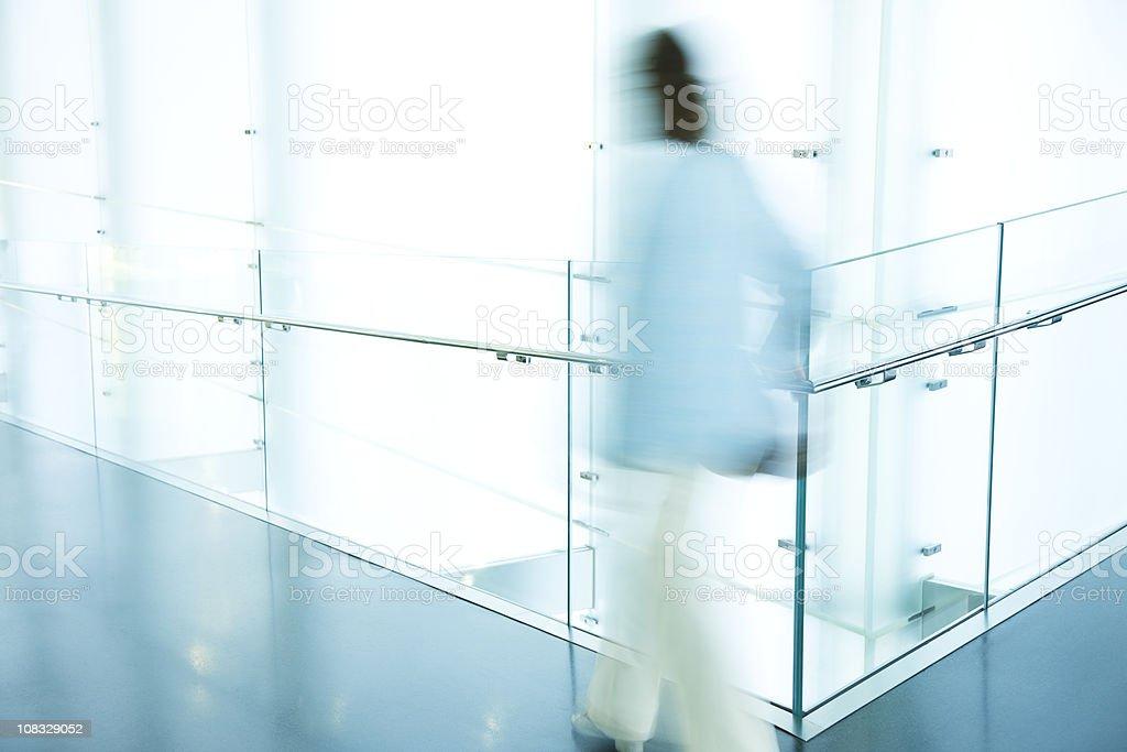 Blurred Woman Walking in Modern Hallway royalty-free stock photo