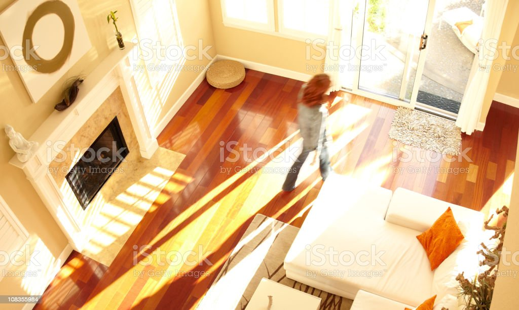 Blurred woman walking through modern living room from above royalty-free stock photo