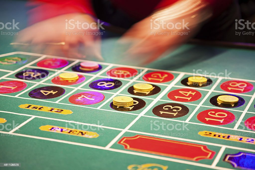 Blurried hands of a dealer placing chips on roulette table royalty-free stock photo