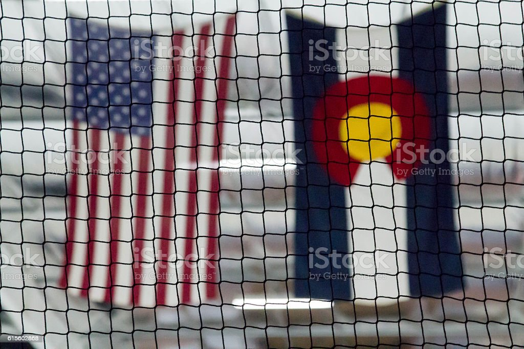 Blurry American and Colorado flags through a black net stock photo