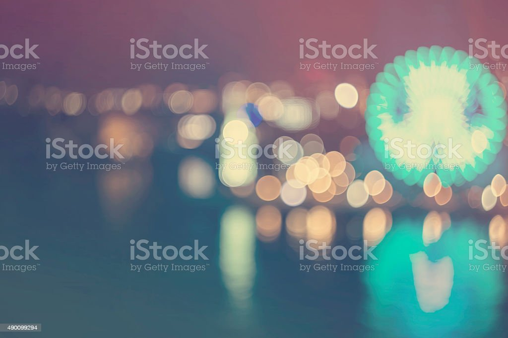 Blurry bokeh night harbor lights background with ferris wheel stock photo
