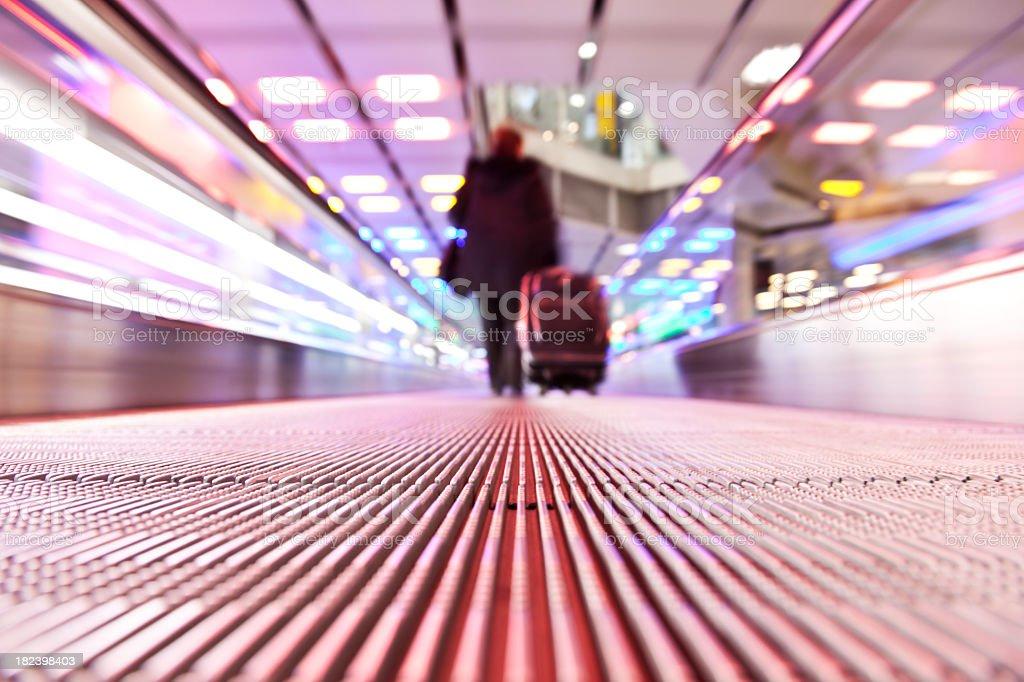 Blurry businessman traveling on horizontal escalator royalty-free stock photo
