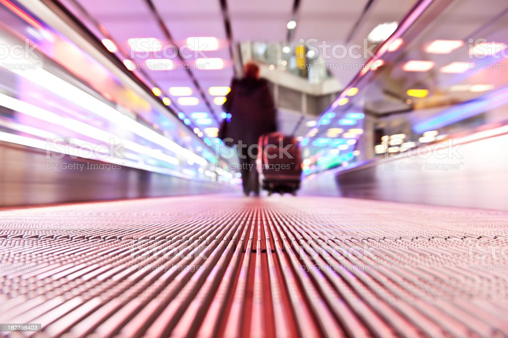 Blurry businessman traveling on horizontal escalator stock photo