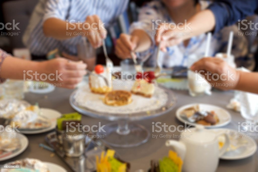 Blurry concept on mature friends having piece of cake stock photo