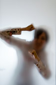 Blurry figure of a woman punching the frosted glass