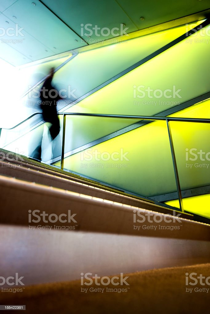 Blurry figure waking down a set of modern stairs stock photo