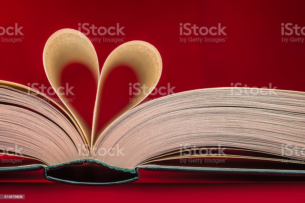 Blurry heart made from book pages over red background stock photo