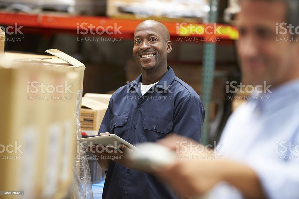 Blurry manager scans a box while a smiling employee looks on stock photo